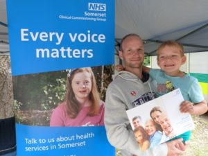image of man and child next to banner with somerset ccg logo and 'every voice matters' written on it.