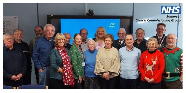 Image of group of people champions of various ages and genders smiling at the camera, pictured with CEO James Rimmer.
