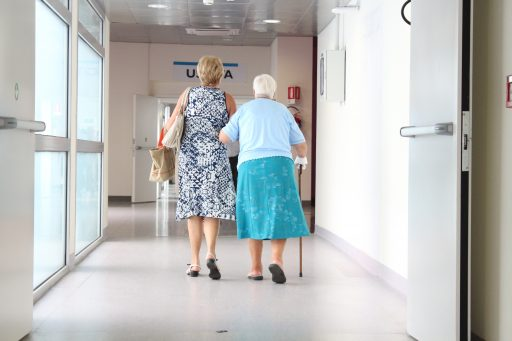 Adult woman walking with her senior mother in hospital corridor