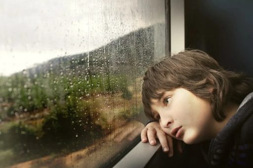Sad boy in train looking out at rain
