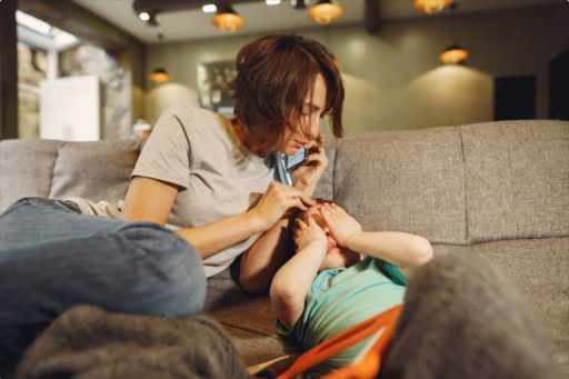 Mother phoning doctor, distressed child on sofa