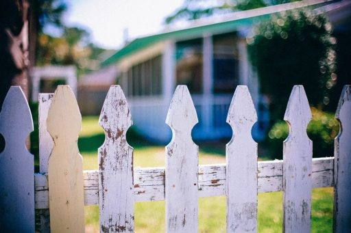 White picket fence with blurred house in background