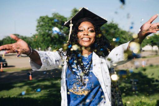 Young black woman in graduation cap celebrating