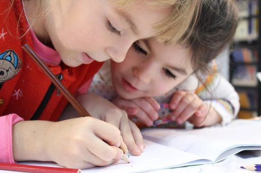 Two children writing together