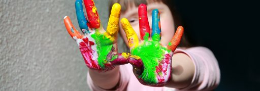 Child with coloured paint over hands