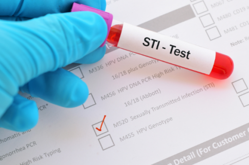 Gloved hand holding STI test tube with questionnaire