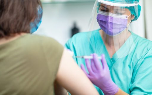 Nurse wearing protective equipment giving flu vaccination to older woman