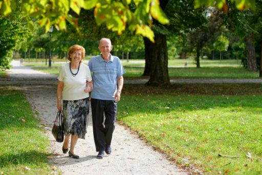 A picture of an older couple walking together through a park
