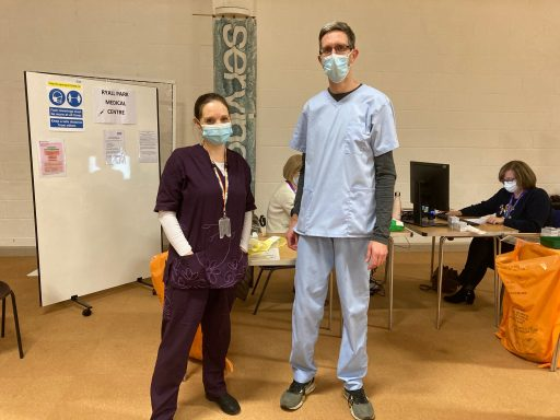 Two staff in PPE at a vaccination hub