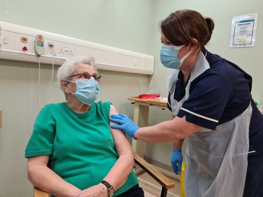 An elderly lady has just received her Covid-19 vaccination at Wincanton Community Hospital - she is looking at the nurse who just vaccinated her
