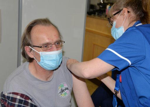 Man in face mask being vaccinated by a nurse