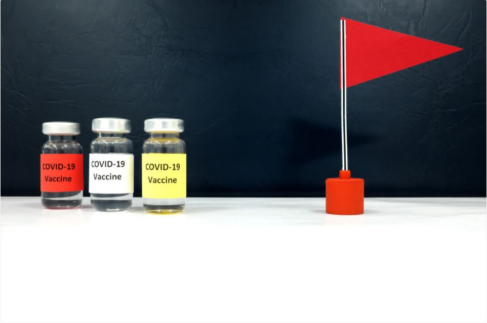 Three vials of vaccine and red flag