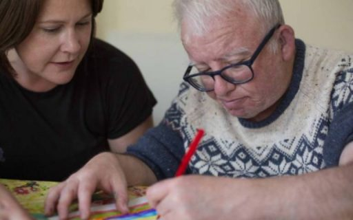 Woman helping older man concentrating on drawing